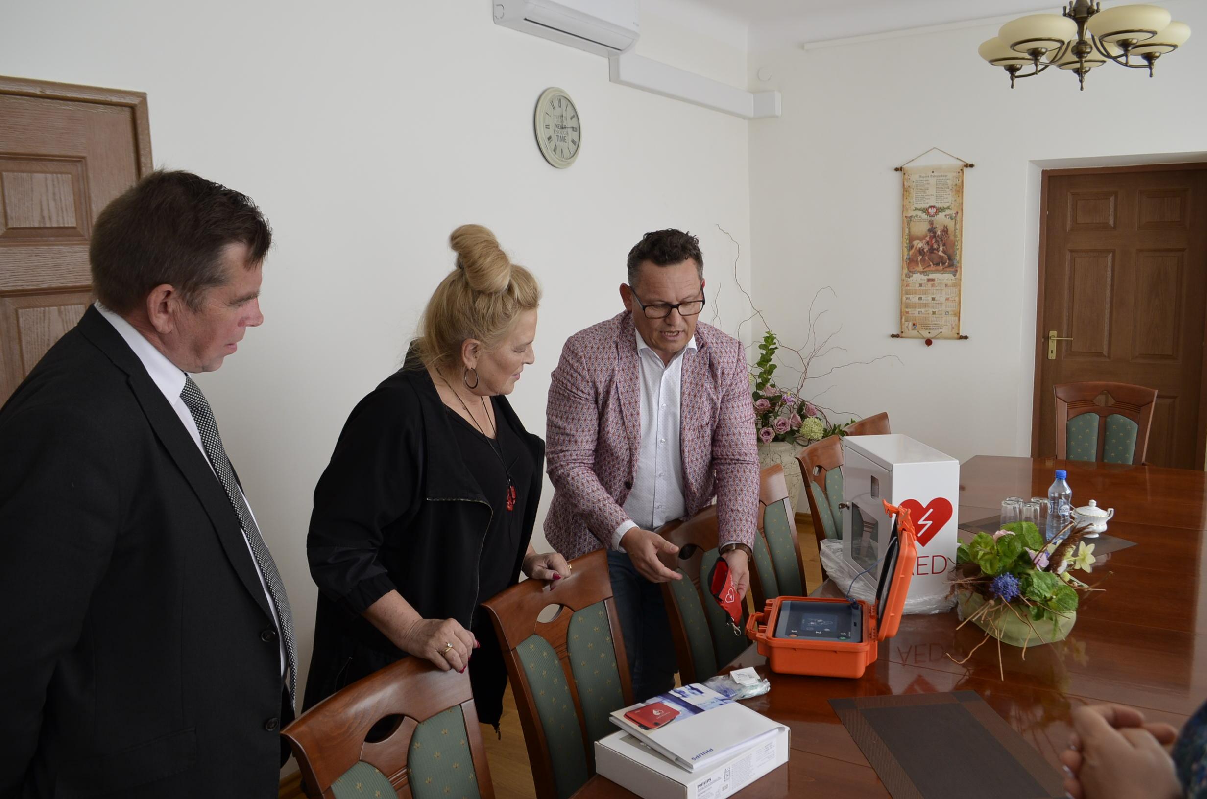 Trzy osoby, jedna przedstawia nowy defibrylator, pozostali się przyglądaja