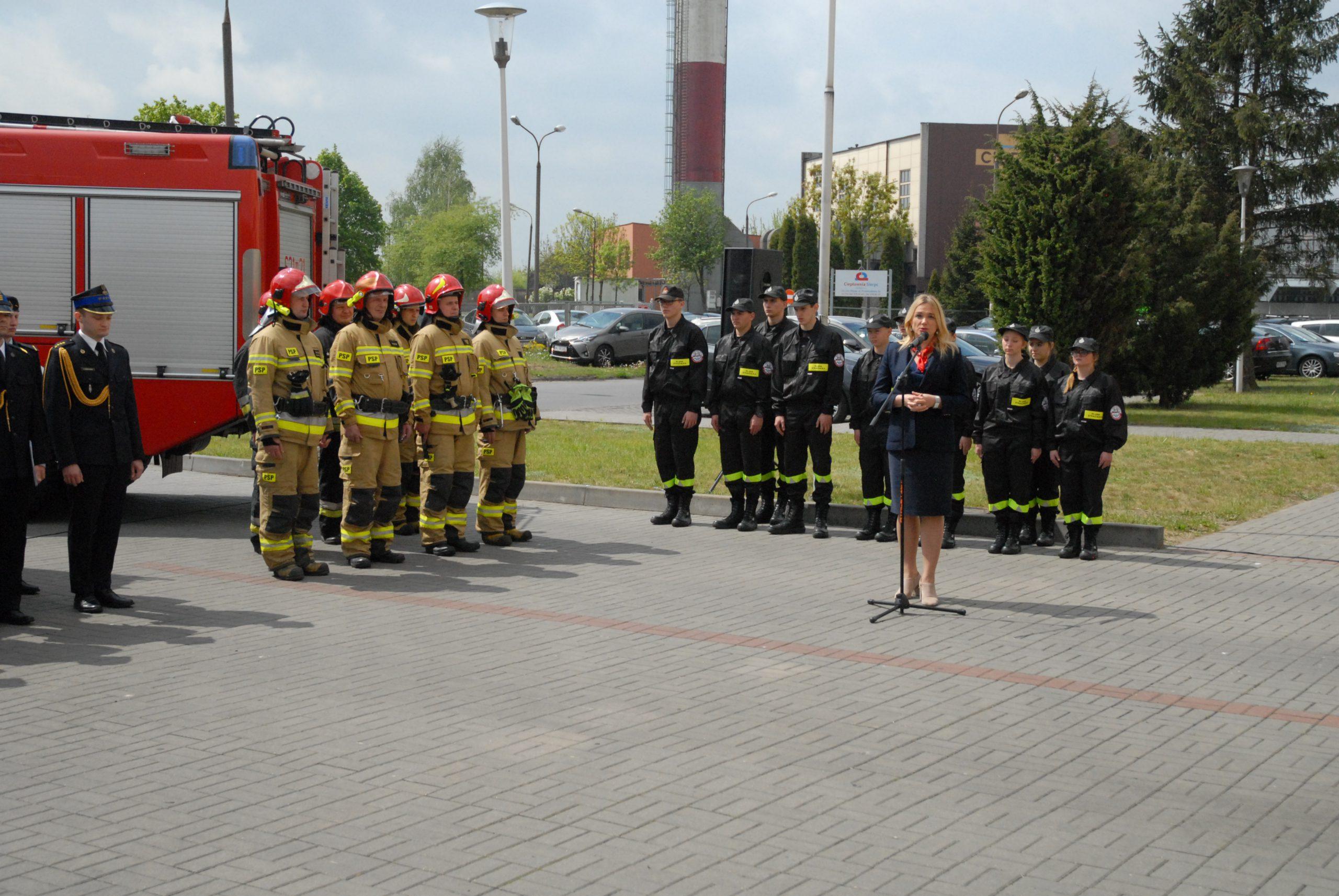 wóz strażacaki a obok nich strażacy w mundurach oraz w strojach strażackich; kobieta przemawia
