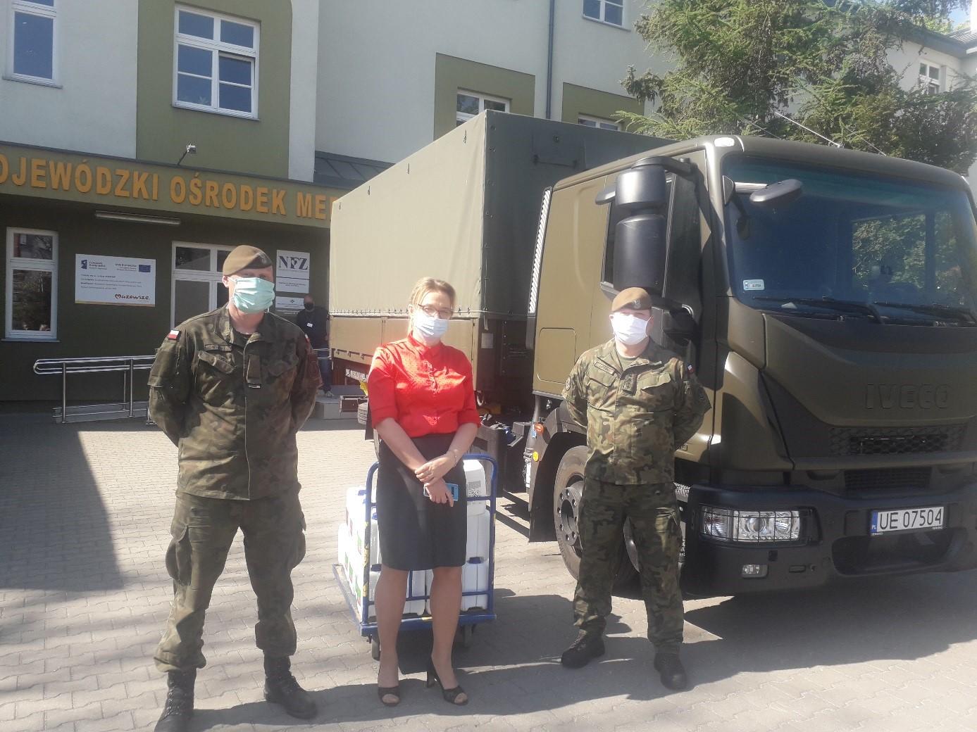 2 żołnierzy oraz dyrektorka stoją na tle przychodni oraz ciężarówki wojskowej; za nimi płyny dezynfekcyjne