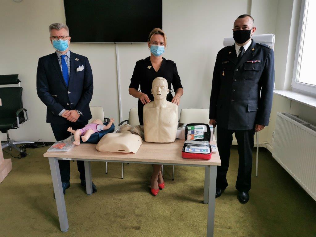 dyrektor Agnieszka Sulkowska wraz z dyrektorem Pawłem Wdówikiem i przedstawicielem straży pożarnej pokazuje fantoma do ćwiczeń RKO